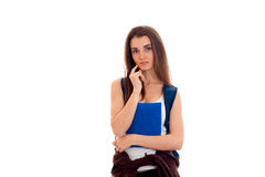 Thoughtful young brunette student with backpack and books in her hands posing on camera isolated on white background Royalty Free Stock Photography