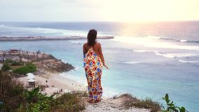 Thoughtful young brunette woman with long hair wearing long dress standing on a rock by the ocean during sunset stock images