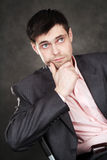 Thoughtful young business man in gray suit. Young business man in gray suit on gray background Royalty Free Stock Photos