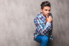 Thoughtful young business man leaning his hand on his leg Royalty Free Stock Photos