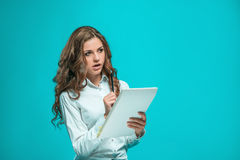 The thoughtful young business woman with pen and tablet for notes on blue background Stock Images