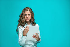 The thoughtful young business woman with pen and tablet for notes on blue background Royalty Free Stock Images