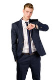 Thoughtful young businessman dressed in a suit looks at watch Royalty Free Stock Images