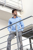 Thoughtful young businessman with hands in pockets standing at hotel balcony Stock Photography