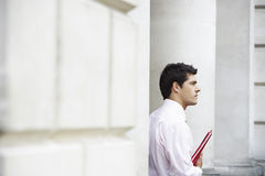 Thoughtful Young Businessman Holding File Stock Photography