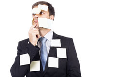 Thoughtful young  businessman with post-it notes on his face and Royalty Free Stock Photography