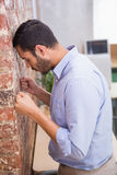 Thoughtful young businessman standing against the wall Stock Photo