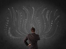 Businessman thinking with sketched arrows in front of a chalkboard Stock Photography