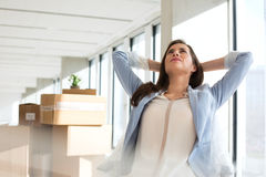 Thoughtful young businesswoman with hands behind head in new office stock photo