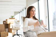 Thoughtful young businesswoman holding coffee cup in new office royalty free stock photos