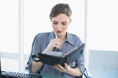 Thoughtful young businesswoman holding a diary sitting at her desk Royalty Free Stock Image