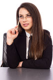 Thoughtful young businesswoman sitting at her desk holding a pen Stock Images