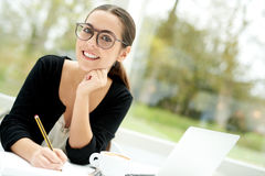 Thoughtful young businesswoman sitting working Stock Images