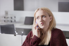 Thoughtful young businesswoman using cell phone at office Royalty Free Stock Images