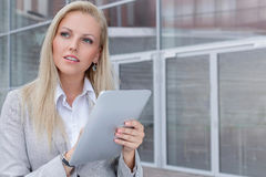 Thoughtful young businesswoman using digital tablet while looking away against office building Royalty Free Stock Photography