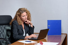 Thoughtful young businesswoman working on a laptop computer Royalty Free Stock Photo