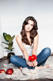 Thoughtful young casual female with red flower. Natural light portrait of young brunette caucasian girl in white casual clothing which sitting on the plaid and Royalty Free Stock Photo