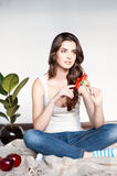 Thoughtful young casual female with red flower. Natural light portrait of young brunette caucasian girl in white casual clothing which sitting on the plaid and stock photo