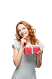 Thoughtful young casual girl with red gift. Young red-haired casual girl with red gift looking away with thoughtful expression on face royalty free stock images