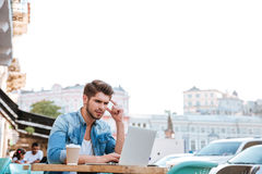 Thoughtful young casual man looking at laptop in cafe outdoors Royalty Free Stock Photos