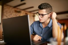 Thoughtful young caucasian businessman in glasses working on laptop computer. Pensive attractive hipster freelancer Stock Photos