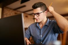 Thoughtful young caucasian businessman in glasses working on laptop computer. Pensive attractive hipster freelancer Stock Photo