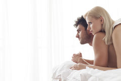 Thoughtful young couple in bed Stock Photo