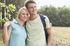 Thoughtful young couple smiling while hiking in forest Stock Photos