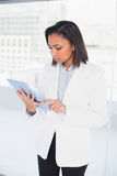 Thoughtful young dark haired businesswoman looking at her tablet pc. In bright office Royalty Free Stock Photo