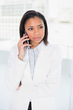 Thoughtful young dark haired businesswoman making a phone call. In bright office Royalty Free Stock Images