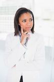 Thoughtful young dark haired businesswoman posing looking away. In bright office Stock Photo