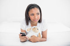 Thoughtful young dark haired model holding a mobile phone and a plush sheep Royalty Free Stock Image