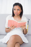 Thoughtful young dark haired woman in white clothes reading a book. In a living room stock photos