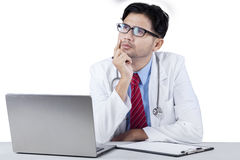Thoughtful young doctor looking upward. Portrait of pensive male doctor looking upward with notebook computer and clipboard on the tablet royalty free stock images