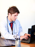 Thoughtful  young doctor working on a computer Royalty Free Stock Photo