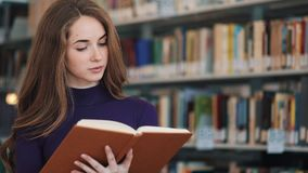Thoughtful young female student reads a book standing in the library stock video