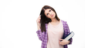 Thoughtful young female student standing with book Royalty Free Stock Images