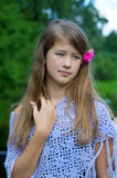 Thoughtful young girl with flower in the hair Royalty Free Stock Photo