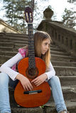 Thoughtful Young Girl With Guitar Sitting on the Stairs and Looking Away Stock Image