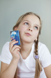 Thoughtful young girl holding credit card over gray background Royalty Free Stock Photography