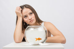 Thoughtful young girl looking at goldfish in a fishbowl Stock Photography