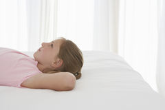 Thoughtful Young Girl Lying In Bed Royalty Free Stock Photos
