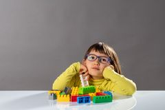 Thoughtful young girl with serious eyeglasses playing with building blocks. On desk for concept of female education in science and engineer career, copy space royalty free stock images