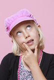Thoughtful young girl wearing cap with finger on chin over pink background Royalty Free Stock Photography