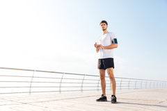 Thoughtful young handsome sportsman standing on the beach pier Royalty Free Stock Images