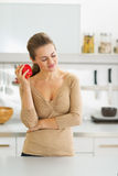 Thoughtful young housewife with apple in modern kitchen Stock Photography