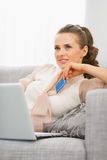 Thoughtful young housewife with laptop and credit card Royalty Free Stock Photography