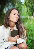Thoughtful Young lady with book. Thoughtful Young lady embracing the book in the hands Stock Photo