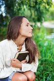 Thoughtful Young lady with book near the river. In half face view stock photos
