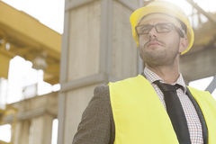 Thoughtful young male architect in protective wear at construction site Royalty Free Stock Photos